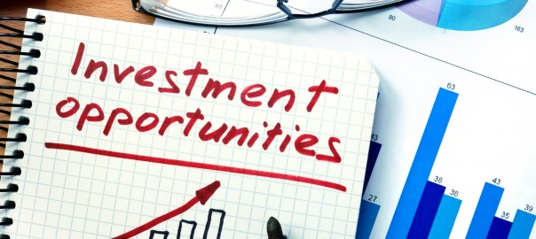 Notepad with investment opportunities   on office wooden table.